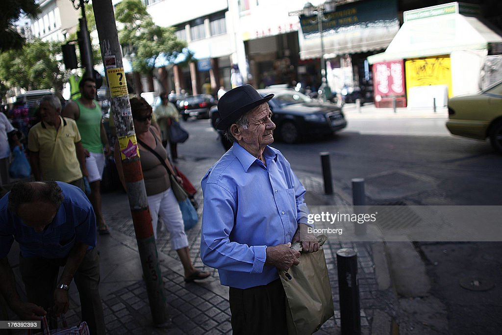 An elderly pedestrian waits to cross a street outside the meat market in Athens, Greece, on Saturday, Aug. 10, 2013. Greece's economy contracted for a 20th quarter, extending an economic slump that has left more than six in 10 young Greeks out of work. Photographer: Angelos Tzortzinis/Bloomberg via Getty Images