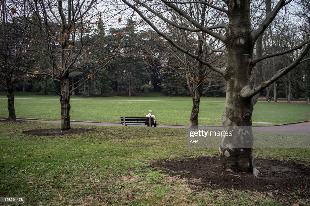An elderly person sits on a public bench, on December 19, 2012 in the Parc de la Tete d Or in Lyon. AFP PHOTO / JEFF PACHOUD