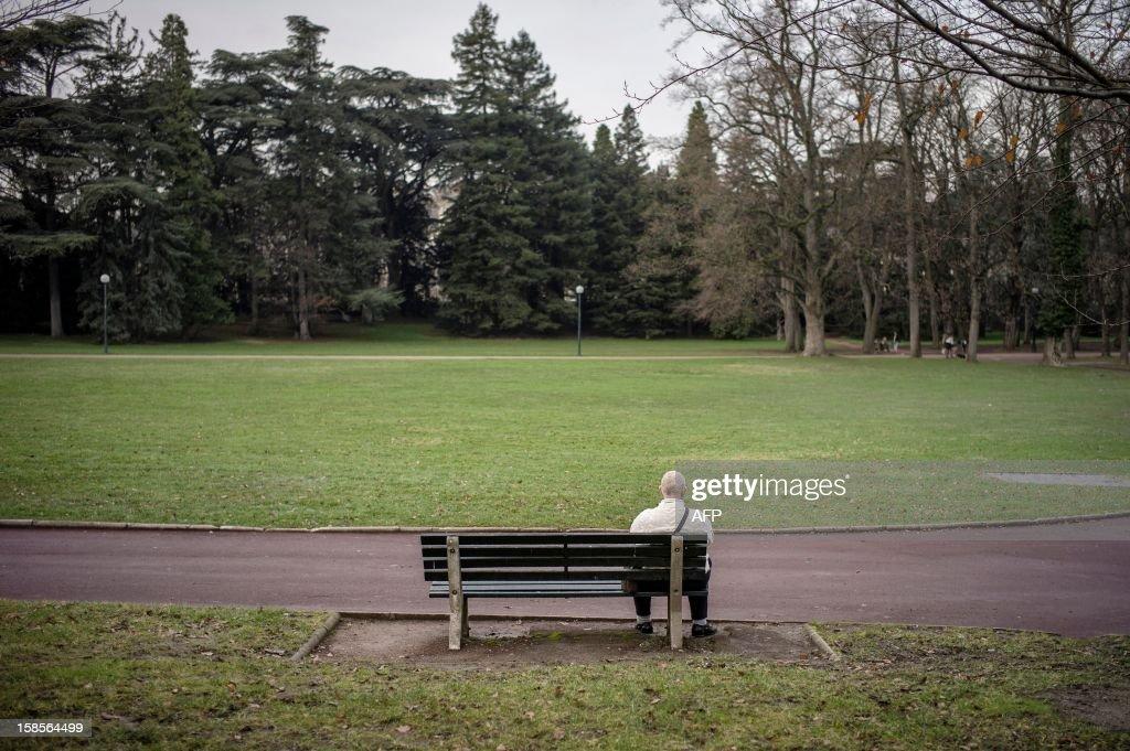 An elderly person sits on a public bench, on December 19, 2012 in the Parc de la Tete d Or in Lyon.