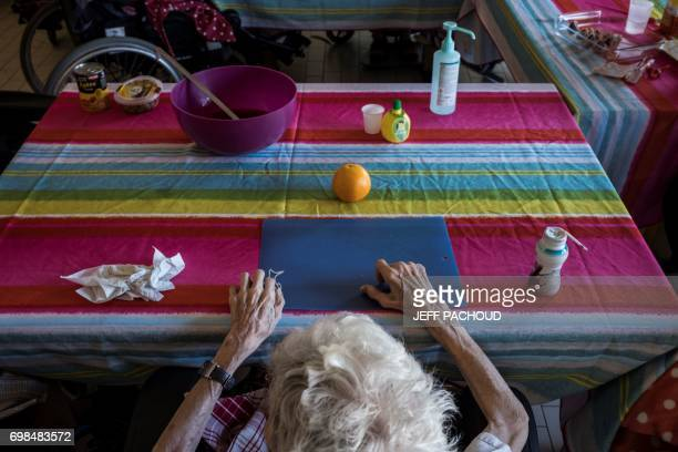 An elderly person takes part in a food activity at the Frederic Dugougeon geriatric unit of the Lyon's CroixRousse hospital on May 24 2017 / AFP...