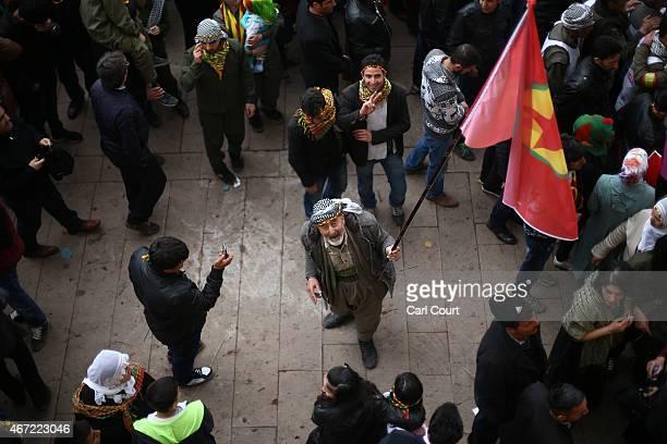 An elderly Peshmerga fighter holds up a PKK flag as he takes part in Kurdish New Year celebrations on March 21 2015 in Diyarbakir Turkey Diyarbakir...
