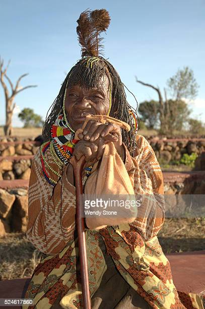 An elderly Pokot woman at the Earth Festivalat the Laikipia Nature Conservancy sits with her cane and wears an elaborate headdress made from ostrich...
