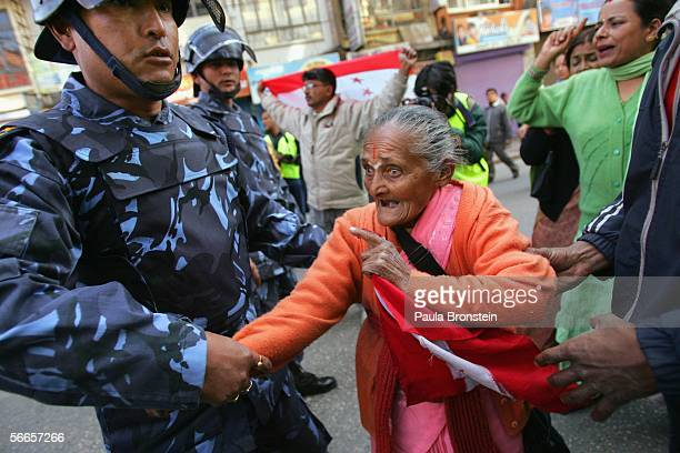 An elderly protester is taken off the street by riot police as she tries to convince them to let her stay during a demonstration protesting the rule...
