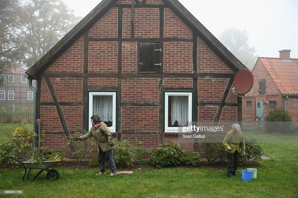 An elderly resident and her daughter do garden work at a house on November 2, 2015 in Sumte, Germany. Sumte, a farming village located southwest of Hamburg, has a population of 102, and starting later today it is to receive 500 migrants who will be housed in an abandoned office park on the village edge. The number of migrants at the shelter could reach up to 750 in coming weeks as Germany struggles to accommodate the unrelenting flood of migrants arriving at a rate of thousands per day. Authorities are distributing migrants seeking asylum in Germany at shelters nationwide, both in urban centers and in small, rural communities.