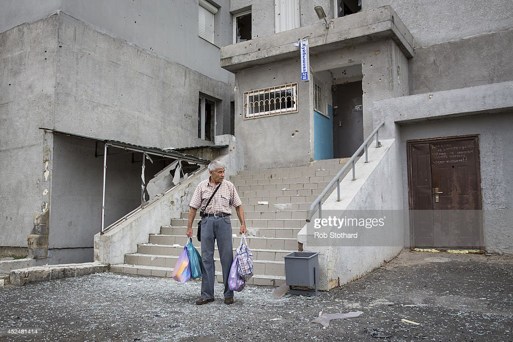 An elderly resident carries some belongings away from his apartment, damaged by shrapnel from a rocket that landed in front of the building on July 21, 2014 in Donetsk, Ukraine. Local authorities warned residents in the area not to go outside or leave their homes whilst intense shelling set a market ablaze close to the station. The security situation is continuing to affect the investigation into the Malaysian Airlines flight MH17 crash and it is still unclear where or when the train containing the bodies of victims will be moved. Malaysian Airlines flight MH17 was travelling from Amsterdam to Kuala Lumpur when it crashed killing all 298 on board including 80 children. The aircraft was allegedly shot down by a missile and investigations continue over the perpetrators of the attack.