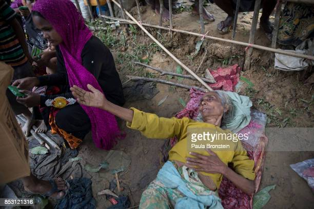 An elderly Rohingya woman begs for humanitarian aid exhausted after arriving by foot from Myanmar September 24 2017 in Thainkhali Cox's Bazar...