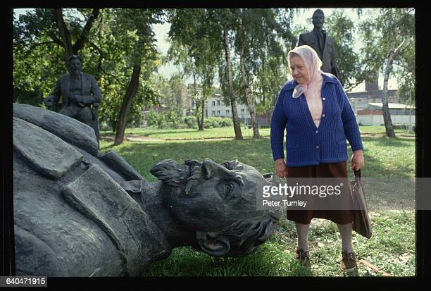 An Elderly Russian woman poses with a 'dead' statue of Felix Dzherzhinsky founder of the modern KGB following the failed coup attempt