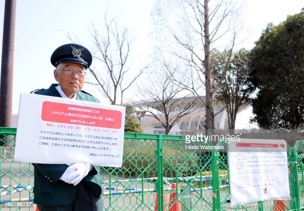 An elderly security guard stands outside the fence not to allow supporters into the restricted area prior to the JLeague match between Urawa Red...