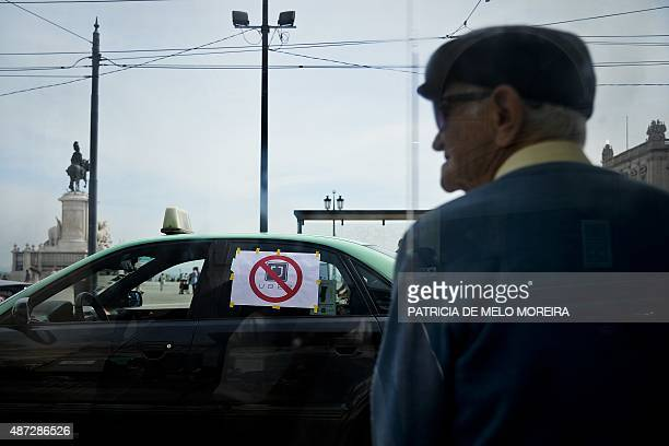An elderly sits at a bus stop during a protest of Portuguese taxi drivers against Uber in Lisbon on September 8 2015 Hundreds of taxi drivers blocked...