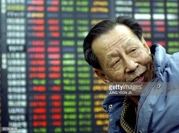 An elderly South Korean man keeps track of the stock index boards at a trading room in downtown Seoul 28 February 2005 South Korean share prices...