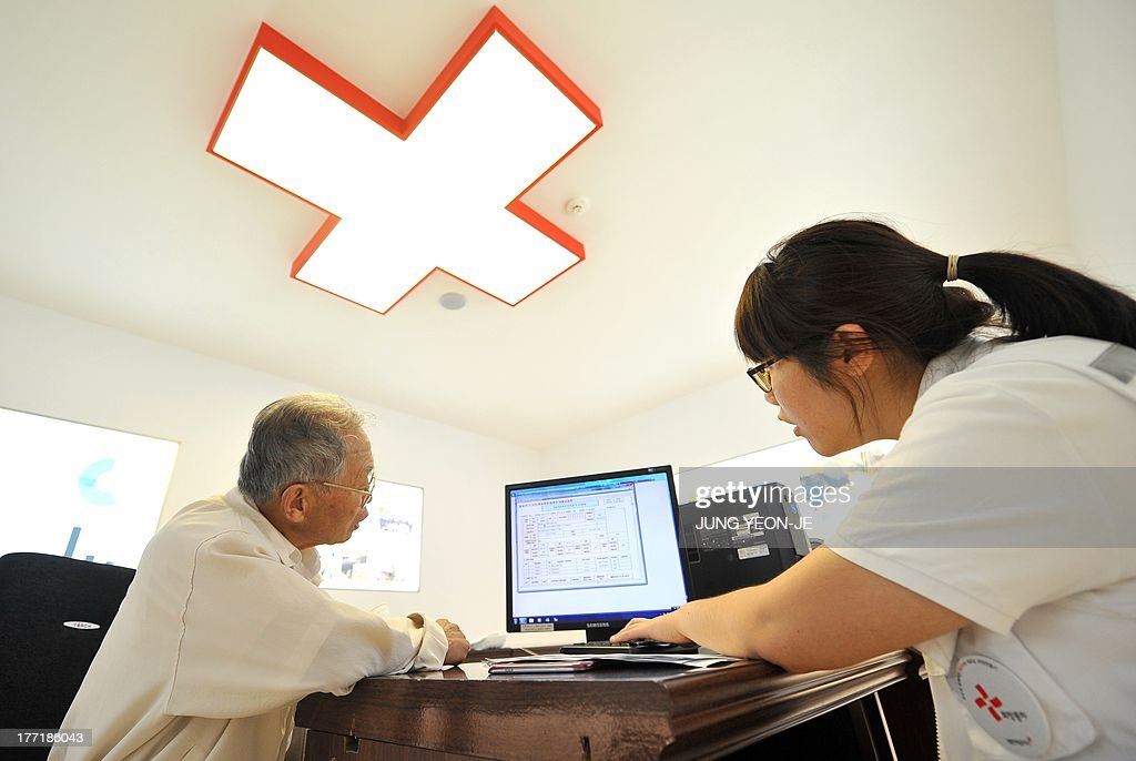 An elderly South Korean man (L) who left behind relatives in North Korea fills out applications for an expected inter-Korean family reunion programme at the Red Cross office in Seoul on August 22, 2013. Red Cross officials from the two Korea will hold talks as planned on August 23 in resuming cross-border family reunions after the North finally agreed to the South's choice of venue.