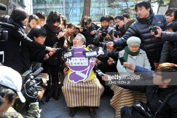 An elderly South Korean woman who served as sex slaves for Japanese soldiers during World War II is surrounded by reporters during a memorial service...
