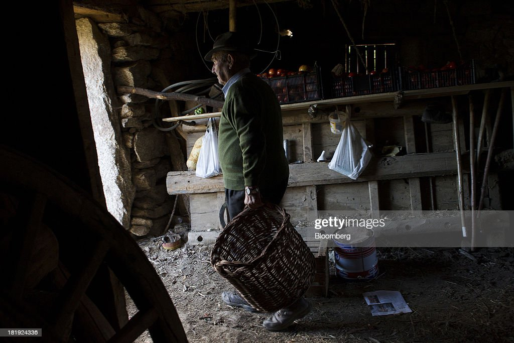 An elderly Spanish man collects a basket from his stores to harvest his onion crop in Bohoyos, Spain, on Thursday, Sept. 26, 2013. Prime Minister Mariano Rajoy is increasingly dependent on the pension reserve fund as it reaps lower returns on Spanish sovereign debt, which comprise 97.5 percent of its investments. Photographer: Antonio Heredia/Bloomberg via Getty Images