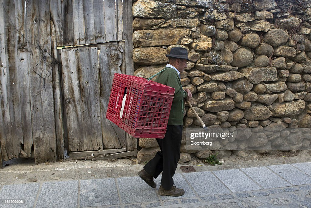 An elderly Spanish man uses his walking stick to carry plastic boxes in Bohoyos, Spain, on Thursday, Sept. 26, 2013. Prime Minister Mariano Rajoy is increasingly dependent on the pension reserve fund as it reaps lower returns on Spanish sovereign debt, which comprise 97.5 percent of its investments. Photographer: Antonio Heredia/Bloomberg via Getty Images