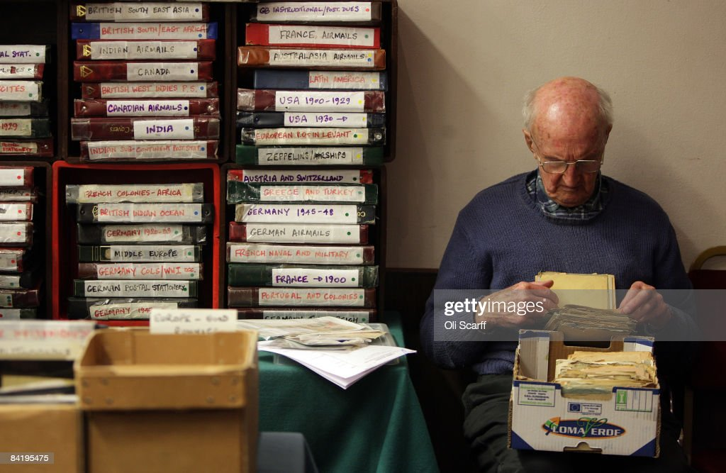 an elderly stamp collector looks through a box of letters for sale at the strand stamp