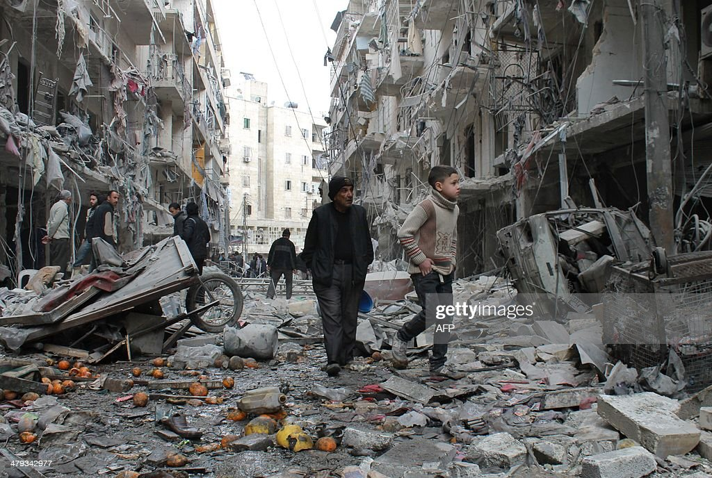 An elderly Syrian man and a child walk amidst debris in a residential block reportedly hit by an explosivesfilled barrel dropped by a government...