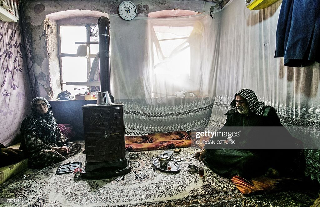 An elderly Syrian refugee couple sit in a house in Basaksehir district of Istanbul, on March 4, 2014. Syrian government forces are waging a campaign of siege warfare and starvation against civilians as part of its military strategy, a UN-mandated probe said on March 5. Syria's war has since March 2011 killed more than 140,000 people and forced millions more to flee.