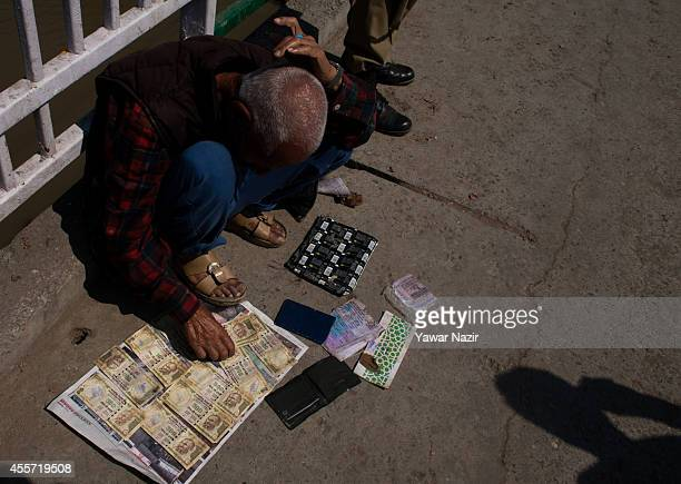 An elderly tailor dries Indian national rupees currency after the flood waters receded on September 19 2014 in Srinagar the summer capital of Indian...