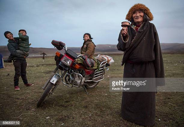 An elderly Tibetan nomad woman swings a prayer wheel as she stands at a temporary camp for picking cordycep fungus on May 22 2016 on the Tibetan...