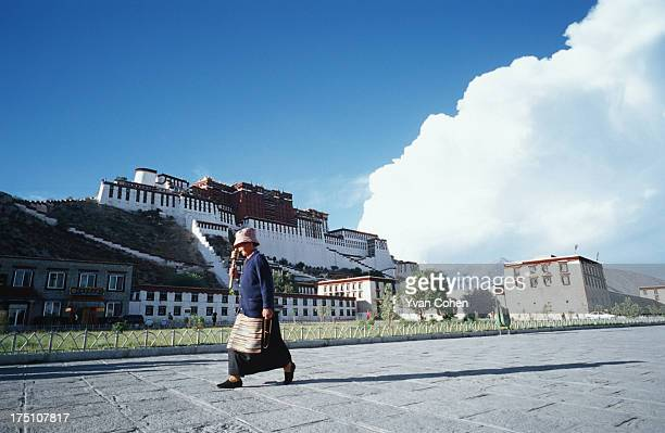 An elderly Tibetan woman spins her prayer wheel as she walks past the Potala palace in Lhasa The palace was once the seat of the Dalai Lama and is...
