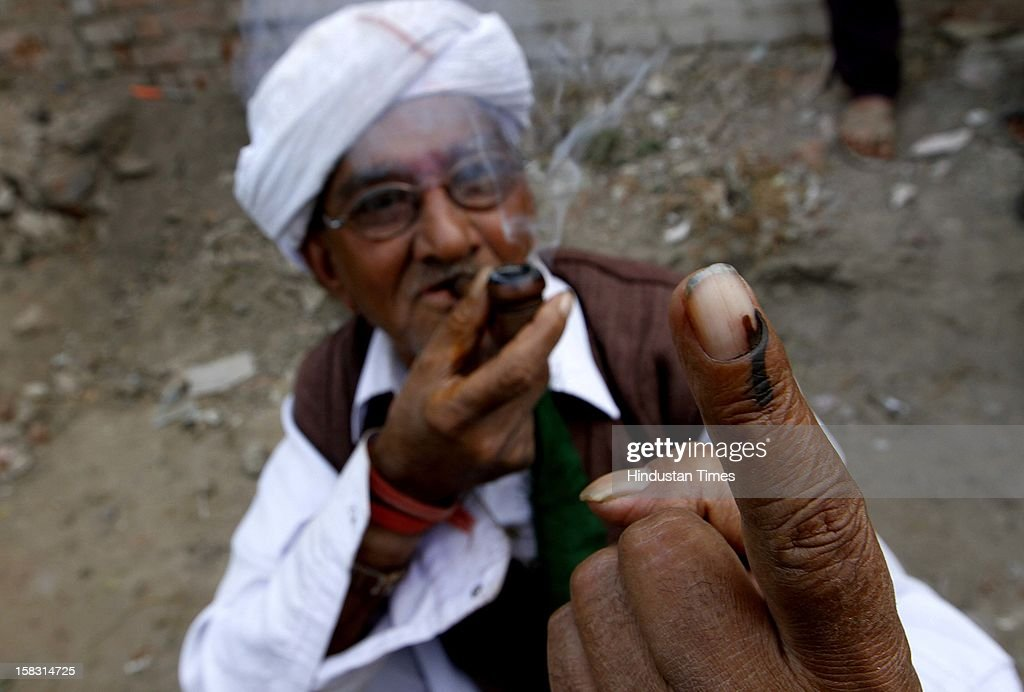 An elderly voter showing the polling mark on his finger after casting vote during the first phase polling of Gujarat assembly election at Sanand on December 13, 2012 in Ahmedabad, India. 13 2012.