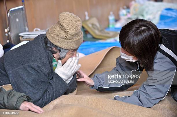 An elderly woman and a relative are reunited at a center for displaced persons in the devastated town of Otsuchi Iwate prefecture on March 18 one...