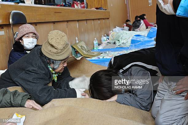 An elderly woman and a relative get emotional as they are reunited at a center for displaced persons in the devastated town of Otsuchi Iwate...