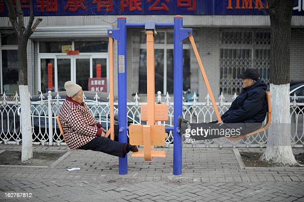 An elderly woman and an elderly man work out with gym equipment by a street in Beijing on February 26 2013 China has vastly expanded health insurance...