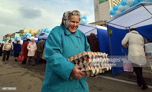 An elderly woman carries eggs packs at a marketpalce in Russian southern city of Stavropol on December 19 2014 Deep recession skyrocketing prices and...
