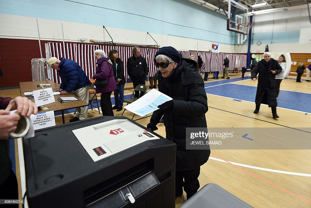 An elderly woman casts her ballot for the first US presidential primary at a school gym in Concord, New Hampshire, on February 9, 2016. New Hampshire voters headed to polls at the snowy break of day on February 9 for the crucial first US presidential primary, with Donald Trump chasing victory and Hillary Clinton looking to narrow the gap on Bernie Sanders. The northeastern state, home to just 1.3 million people, sets the tone for the primaries -- and could shake out a crowded Republican field as the arch-conservative Senator Ted Cruz and establishment candidates led by Marco Rubio battle for second place behind the frontrunner Trump. / AFP / Jewel Samad