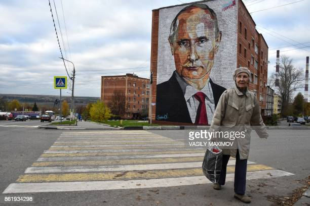 An elderly woman crosses a road in front a mural painting depicting Russian President Vladimir Putin on the wall of a house in the town of Kashira...
