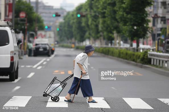 An elderly woman crosses a street in Kita ward in Tokyo Japan on Tuesday June 16 2015 Tokyo is one of only four cities among the 71 mostpopulous...