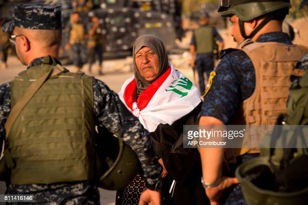 An elderly woman draped in Iraq's na tional flag looks on as she stands by Iraq's federal police members celebrating in the Old City of Mosul on July...