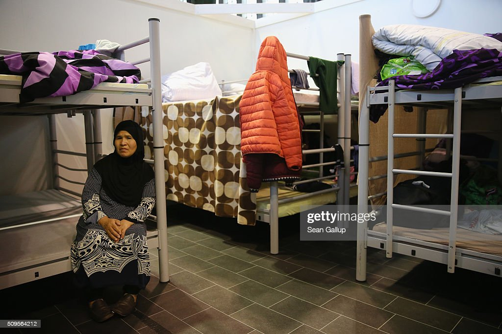 An elderly woman from Afghanistan sits on a bunk bed in the cubicle she shares with other family members in Hangar 7 at former Tempelhof Airport on February 11, 2016 in Berlin, Germany. Tempelhof, once an airport in the city center and first built in the 1930s, now houses approximately 2,600 refugees in three former hangars. Berlin city authorities recently approved plans to expand its capacity to house the newcomers with an additional 90 shelters with space for 30,000 people. An estimated 50,000-80,000 migrants and refugees already live in Berlin. Germany received 1.1 million refugees and migrants in 2015 and is expecting to continue to receive large numbers in 2016.