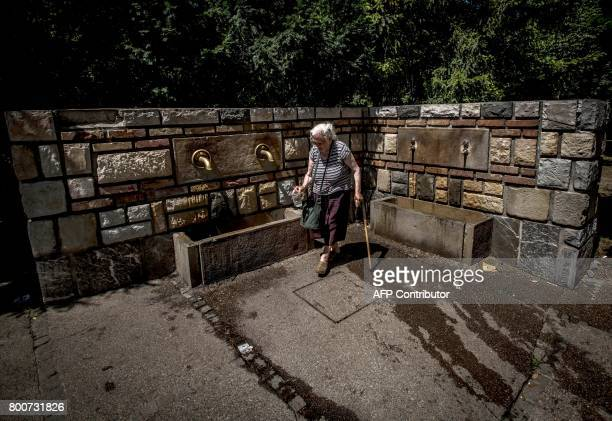 An elderly woman gets water from a public tap at a park in the Serbian capital Belgrade on June 25 2017 as a heat wave sweeps the country with...