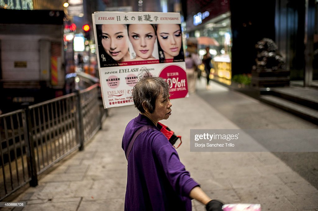 An elderly woman gives flyers to the pedestrians on August 19, 2014 in Hong Kong, Hong Kong. A government-commissioned study headed by University of Hong Kong academic Nelson Chow Wing-sun proposed to fund HK $3,000 a month pension for every Hongkonger over 65, rich or poor, without a means test. The pension should be funded partly by contributions ranging from 1 to 2.5 per cent of employees' salaries, paid by employers and workers. One in three old people in Hong Kong lives below estimated poverty line some of them struggling to make a living collecting cardboard boxes and plastic bottles on the street.