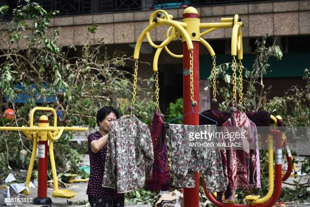 An elderly woman hangs her clothes to dry at a public playground in Macau on August 24 a day after Typhoon Hato hit the city The death toll from...