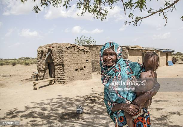 N'DJAMENA CHAD JUNE 22 An elderly woman holding a baby is seen in a village near the capital N'djamena Chad on June 22 2015 Around %85 of the people...