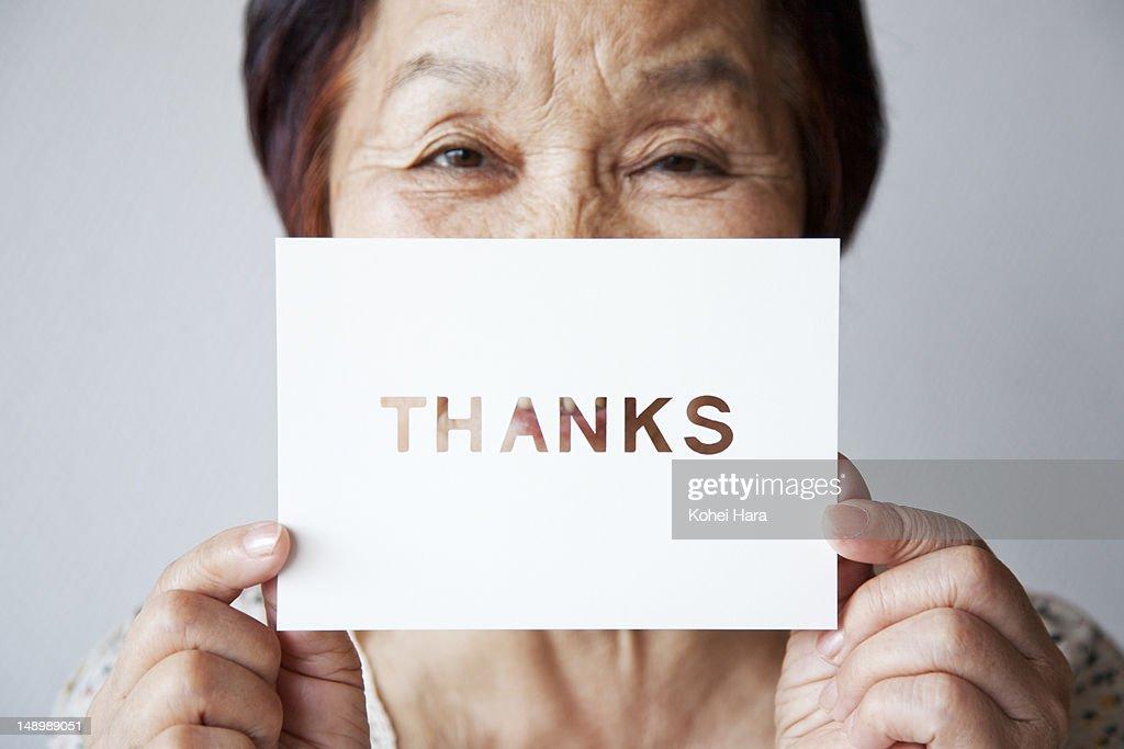 an elderly woman holding a card : Stock Photo