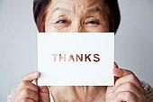 an elderly woman holding a card