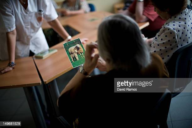 An elderly woman holds a picture of a sheep as she try to remenber the name of the animal during a memory activity at the Cuidem La Memoria elderly...