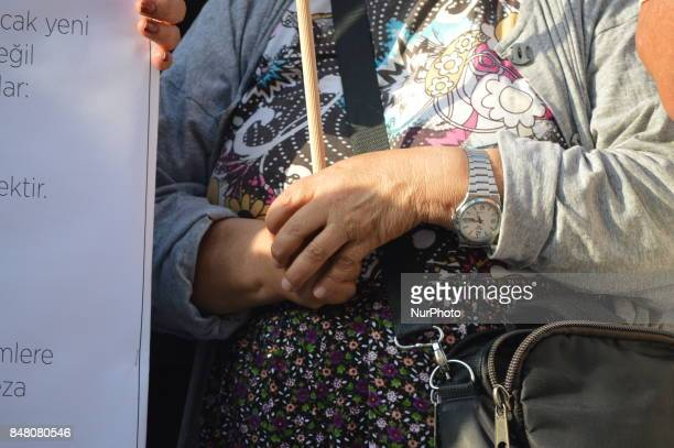 An elderly woman holds a placard as people protest against the Turkish government's new education policies in Ankara Turkey on September 16 2017 The...