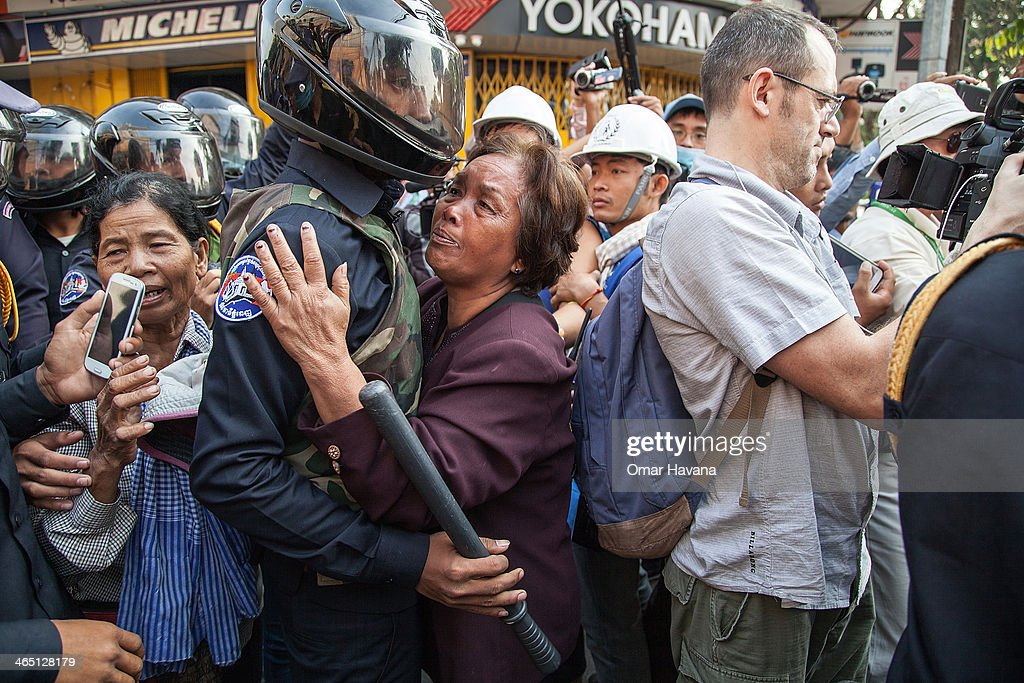 An elderly woman hugs a member of the municipal security forces after having been pushed away during a demonstration to re-take the opposition's base, Freedom Park, on January 26, 2014 in Phnom Penh, Cambodia. Anti-government protestors clashed with Security forces as they attempted to gather early Sunday morning in Phnom Penh's Freedom Park, days after supporters of the opposition Cambodian National Rescue Party were violently evicted by security forces. The Anti-government protestors have been using the park since the last general elections in July 2013 as a central rallying point in the Cambodian capital, from where to organise mass demonstrations, demanding a resolution to the political deadlock in Cambodia.