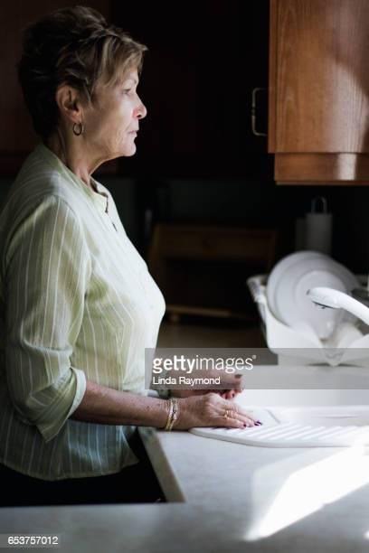 An elderly woman in her kitchen looking throw a window