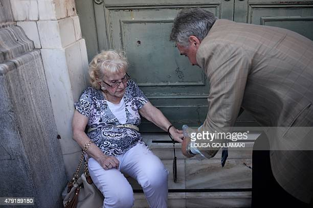 An elderly woman is assisted by an employee from the National bank of Greece in Athens after she felt unwell while waiting in line to get her pension...