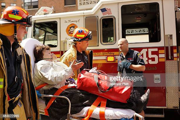 An elderly woman is brought to an ambulance after a fire on the fourth floor of a high rise apartment building in the Brighton Beach neighborhood of...