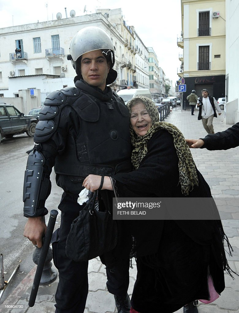 An elderly woman is escorted away from tear gas smoke by a riot policeman during clashes between Tunisian police and protesters following a rallye outside the Interior ministry to protest after Tunisian opposition leader and outspoken government critic Chokri Belaid was shot dead, on February 6, 2013 in Tunis. The protesters, who massed on Habib Bourguiba Avenue, epicentre of the 2011 uprising that ousted ex-dictator Zine El Abidine Ben Ali, pelted the police with bottles and the police responded by firing tear gas, chasing the protesters and beating them with batons.