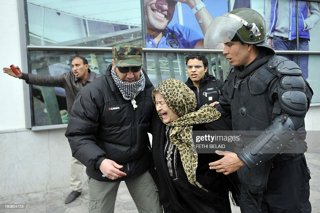 An elderly woman is escorted away from tear gas smoke during clashes between Tunisian police and protesters following a rallye outside the Interior ministry to protest after Tunisian opposition leader and outspoken government critic Chokri Belaid was shot dead, on February 6, 2013 in Tunis. The protesters, who massed on Habib Bourguiba Avenue, epicentre of the 2011 uprising that ousted ex-dictator Zine El Abidine Ben Ali, pelted the police with bottles and the police responded by firing tear gas, chasing the protesters and beating them with batons.