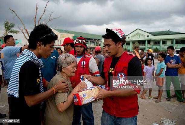 An elderly woman is given her ration as Red cross volunteers distribute food parcels in Dagami some 35kms inland south of Tacloban on November 18...