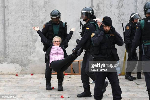 An elderly woman is removed by force as police move in on the crowds as members of the public gather outside to prevent them from stopping the...